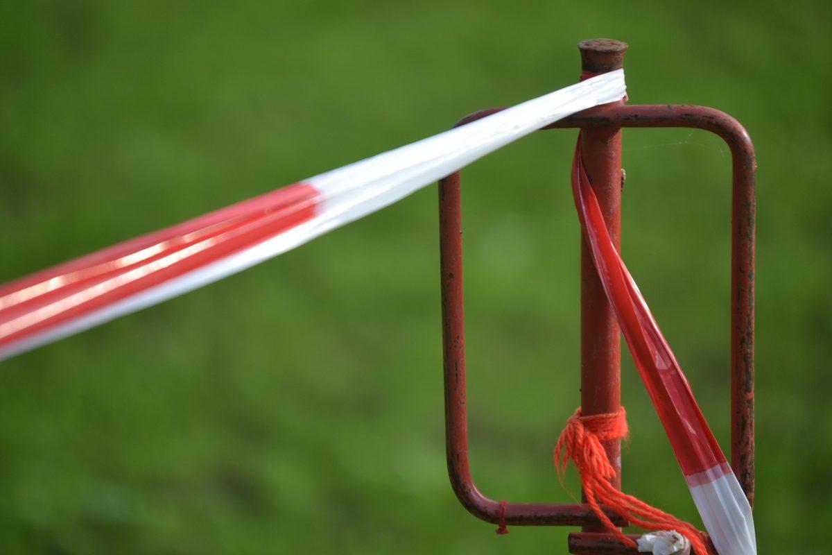 Ein Absperrband festgebunden an einem roten Pfahl.
