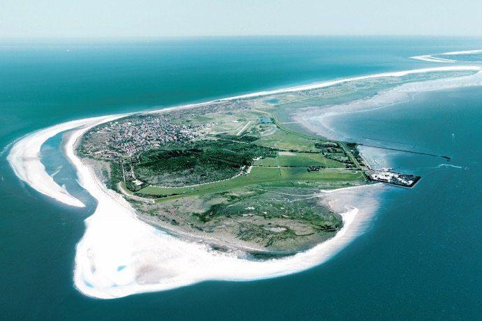 Die Insel Langeoog aus der Vogelperspektive umrandet vom Meer.