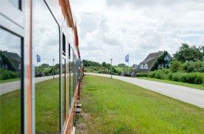 Ausblick aus der Inselbahn Langeoog. Man sieht viel grüne Natur und ein Haus.