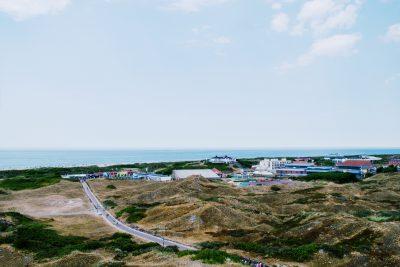 Aussicht auf die Insel Langeoog. Man sieht die Hügel, Innenstadt und das Meer