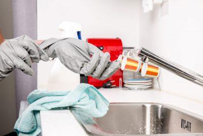 Eine Frau zieht sich an der Spüle die Gummihandschuhe aus. Neben ihr stehen Putzutensilien.