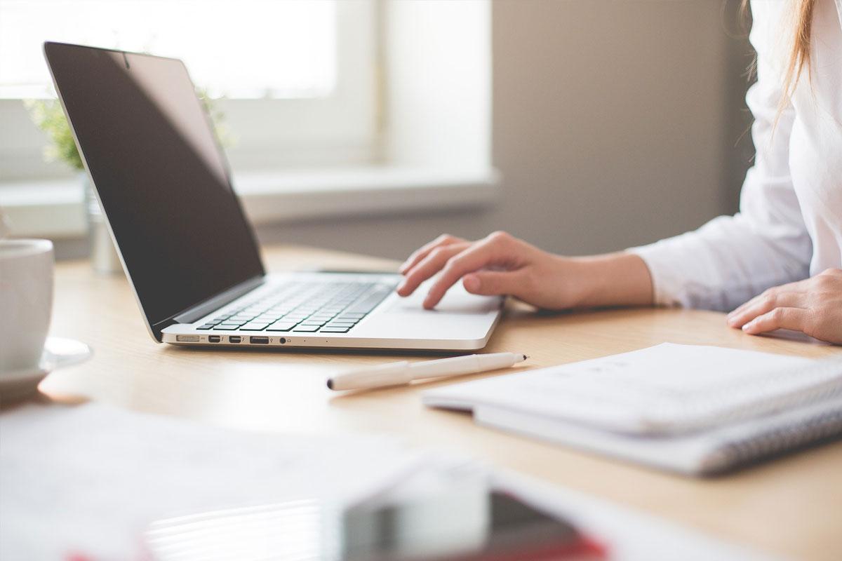 Eine Frau sitzt am Schreibtisch und bedient ihren Laptopt über das Mousepad
