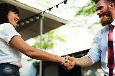 Eine Frau und ein Mann in Business-Kleidung schütteln sich die Hand und lächeln einander an.