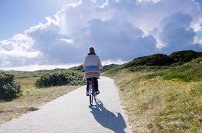 Eine Frau fährt in der Natur Fahrrad.