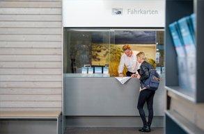 Eine Touristin wird am Fahrkartenschalter von einem Mitarbeiter beraten.