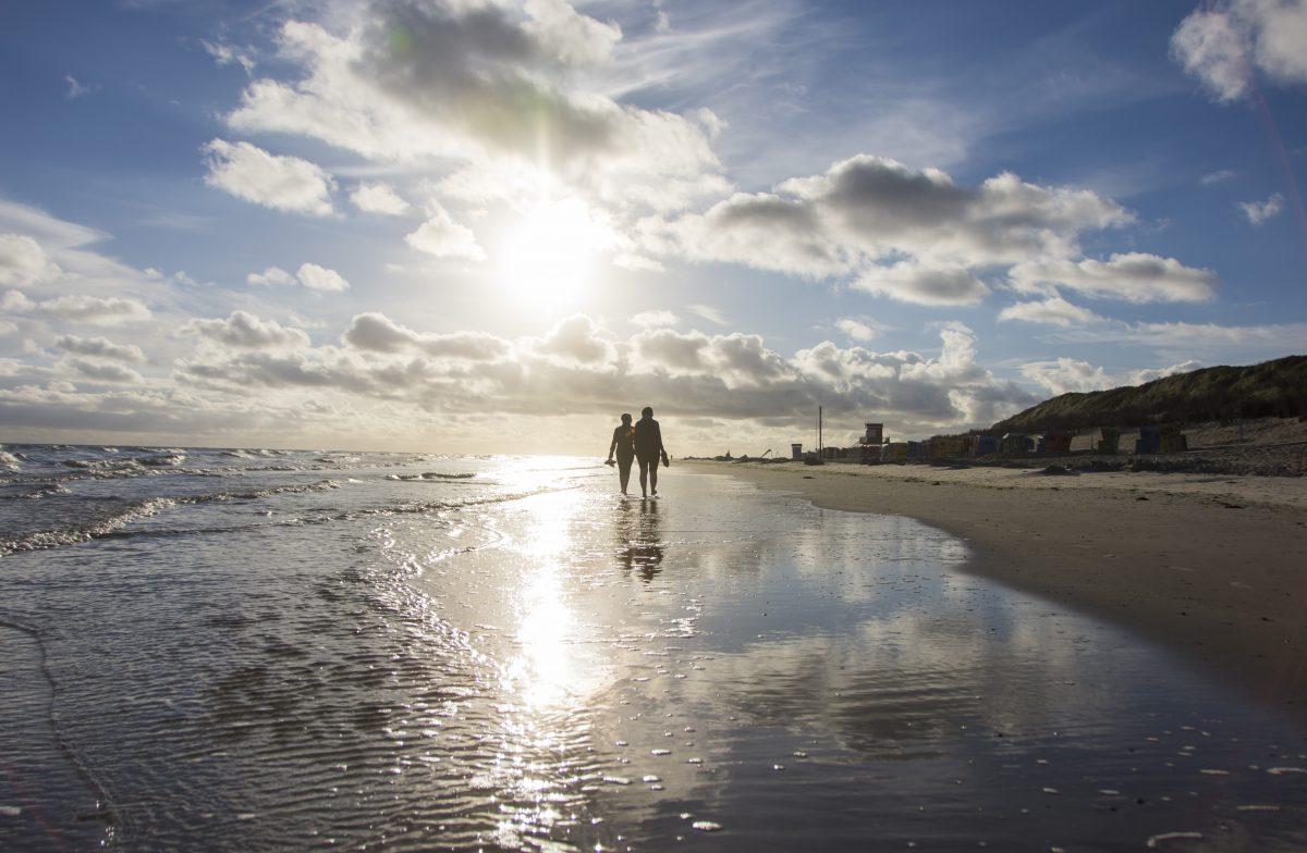 Ein Pärchen geht Barfuß am Meeresufer spazieren und laufen der Sonne entgegen.