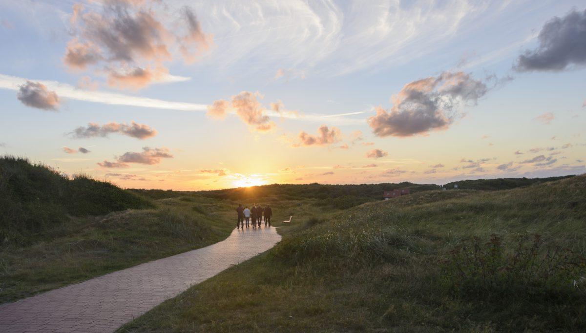 Eine Wandertruppe läuft durch die Dünen von Langeoog in Richtung Sonnenuntergang