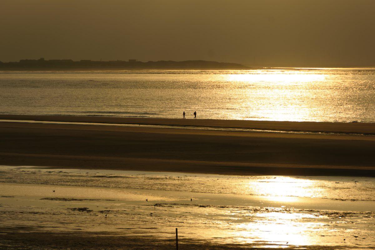 Zwei Menschen laufen am Meeresufer entlang und der Sonnenuntergang spiegelt sich im Wasser