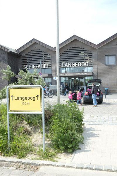 Das Gebäude der Schiffahrt Langeoog in der außenansicht. Vor dem Gebäude sind Menschen zu sehen, die Ihr Gepäck aus dem Kofferraum eines schwarzen Autos holen.