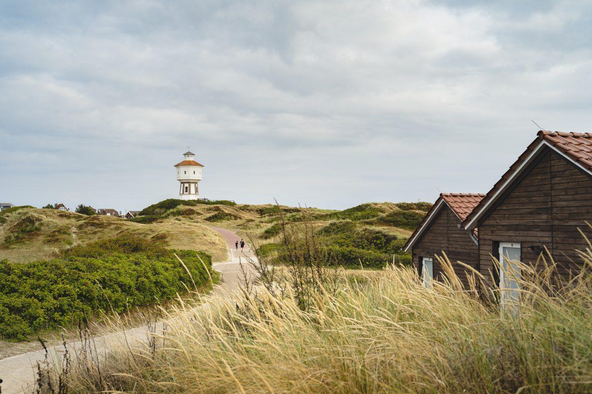 Zwei kleine Hütten in der Dünenlandschaft. Ein Weg mit Spaziergängern führt in Richtung Wasserturm.
