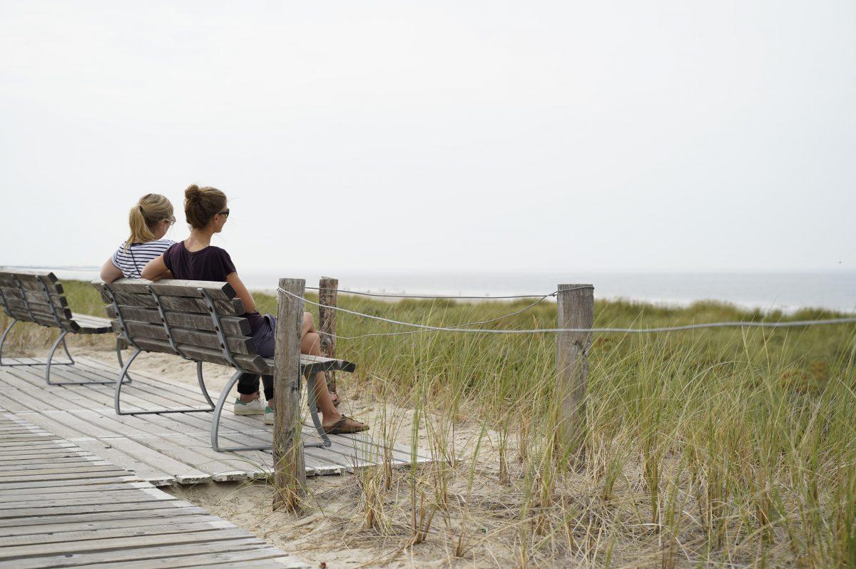 Zwei Frauen sitzen gemeinesam auf einer Bank im Gras und schauen aufs Meer raus