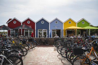 Eine kleine Reihe mit bunten Häusern, die verschiedene Geschäfte beherbergen. Die linken Häuser sind rot, die in der Mitte blau und rechts gibt es noch ein gelbes und ein grünes Häuschen. Hier sitzen viele Menschen draußen an Tischen mit Sonnenschirmen. Ein Zaun trennt diesen bereich von den Fahrradständern ab. Dort stehen sehr viele Fahrräder.