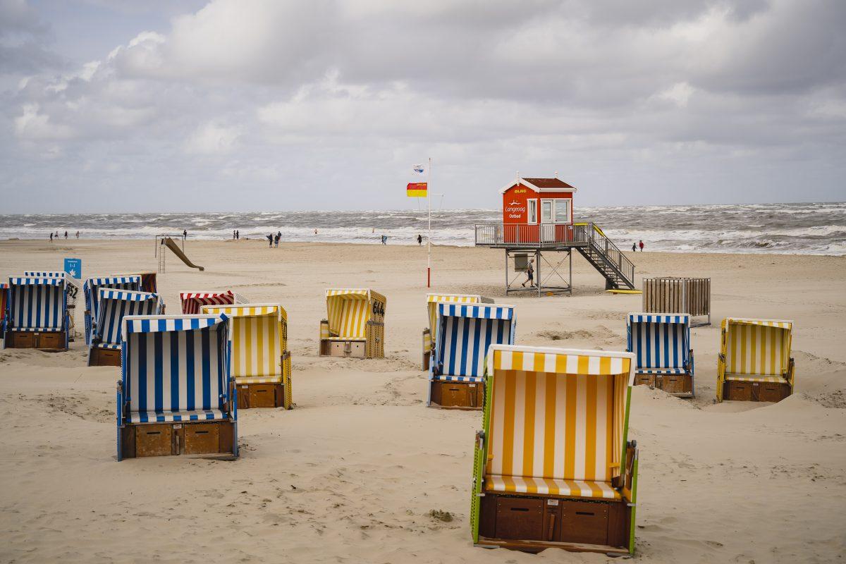 Sehr viele Strandkörbe in den Farben rot, gelb und blau stehen vor dem Strandhäuschen der DLRG am Langeooger Strand