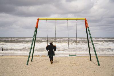 Eine Frau schaukelt auf einer Schaukel direkt am Meer.