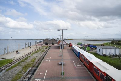 Der Anlegepunkt der Fähren aus der Froschperspektive. Man sieht den Durchgang der Schiffahrt Langeoog, die Inselbahn, Bahngleise, einen großen Bahnhofsplatz, eine grüne Landschaft und das Meer