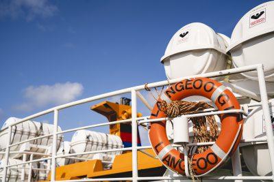 """Die Sicht auf eine Fähre mit einem orangenen Rettungsring mit der Aufschrift """"Langeoog"""""""